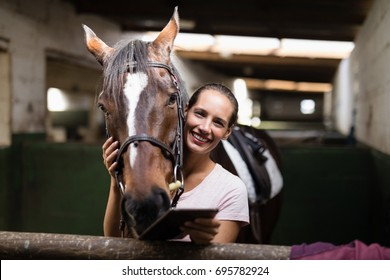 Portrait of smiling female jockey holding tablet computer while standing by horse in stable