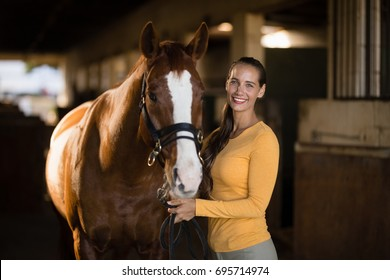Portrait of smiling female jockey standing by horse in stable