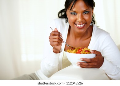 Portrait of a smiling female looking at you and having healthy breakfast while is sitting on sofa at home indoor. with copyspace