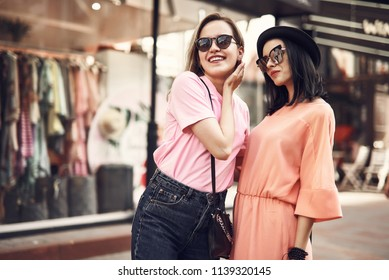 Portrait of smiling female in modern sunglasses situating near modern shop with clothes. Fashion concept