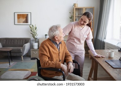 Portrait of smiling female nurse helping senior man in wheelchair at retirement home, copy space