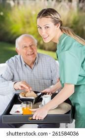 Portrait of smiling female nurse serving breakfast to senior man in nursing home