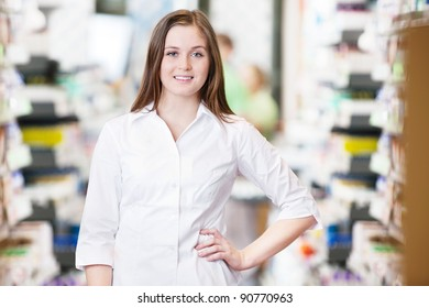 Portrait of smiling female pharmacist standing with hand on hip
