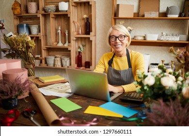 Portrait of smiling female small business owner using laptop and looking at camera in flower shop, copy space