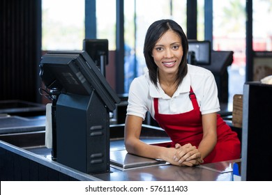 Portrait of smiling female staff sitting at cash counter in supermarket