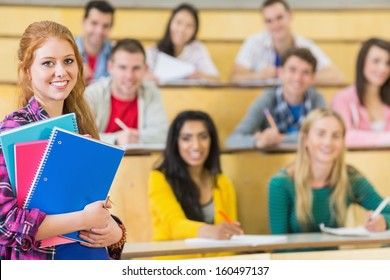 Portrait of a smiling female with students sitting at the college lecture hall