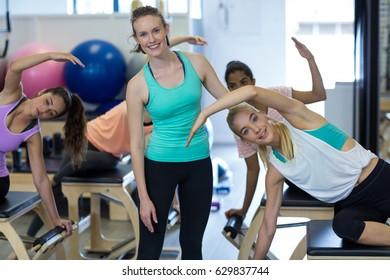 Portrait of smiling female trainer assisting woman with exercise in gym