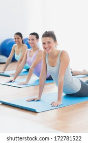 Portrait of a smiling fit class doing the cobra pose in a bright fitness studio
