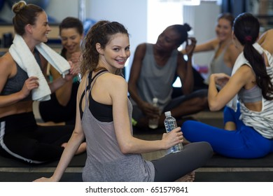 Portrait of smiling fit woman relaxing in gym