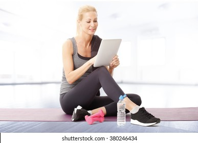 Portrait of smiling fit woman using digital tablet while sitting at yoga mat after fitness workout.