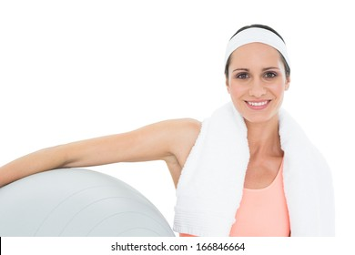 Portrait of a smiling fit young woman holding fitness ball over white background
