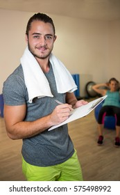 Portrait of smiling fitness trainer writing on clipboard in fitness studio