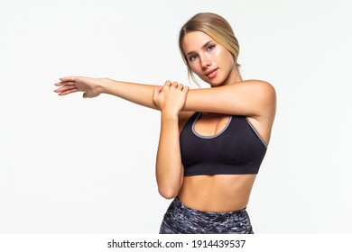 Portrait of a smiling fitness woman stretching her hands isolated over white background