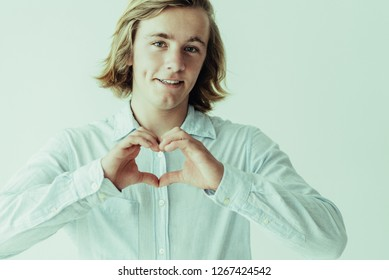 Portrait of smiling flirty guy in love. Young Caucasian blonde man gesturing heart with fingers. Romance and gesturing concept