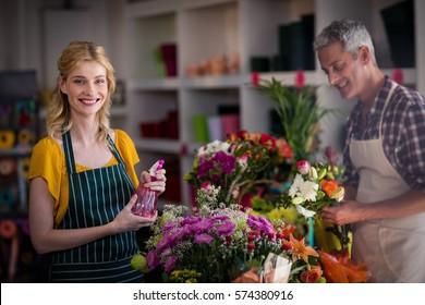Portrait of smiling florist spraying water on flowers in flower shop