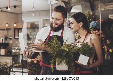 Portrait of smiling florists man and woman. Young bearded man and beautiful smiling girl florists looking design and concept for a bouquet of flowers on a laptop. Flower business concept