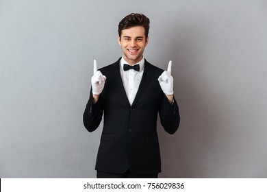 Portrait of a smiling friendly man dressed in tuxedo and gloves pointing two fingers up isolated over gray background
