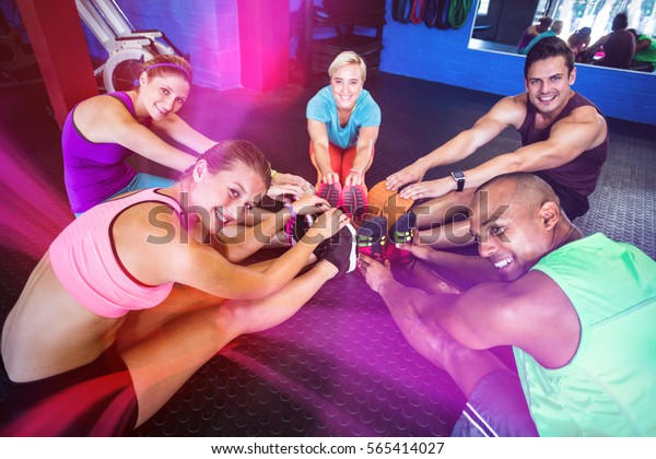 Portrait of smiling of friends stretching while sitting in gym