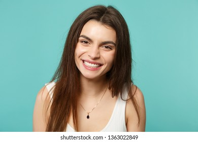 Portrait of smiling funny cute young woman in light casual clothes looking camera isolated on blue turquoise wall background in studio. People sincere emotions, lifestyle concept. Mock up copy space