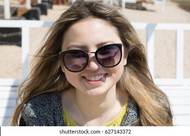 Portrait of a smiling girl in black glasses close-up on the street