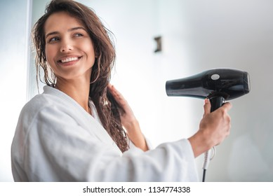 Portrait of smiling girl blowing wind on wet hair while holding hairdryer in hands