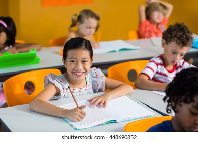 Portrait of smiling girl with book on bench in classroom