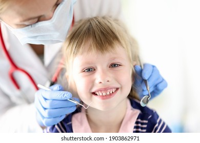 Portrait of smiling girl at dentist appointment. Treatment of baby milk teeth concept