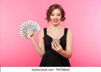 Portrait of a smiling girl dressed in black dress holding bunch of money banknotes and looking at mobile phone isolated over pink background