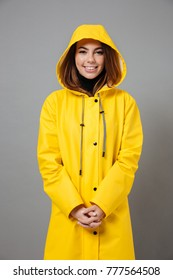 Portrait of a smiling girl dressed in raincoat posing with hood on her head and looking at camera isolated over gray background