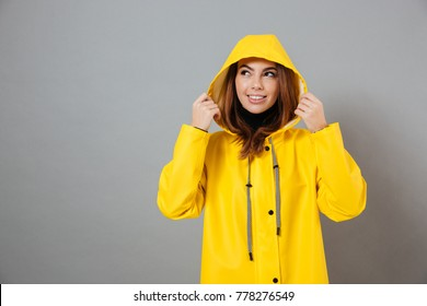 Portrait of a smiling girl dressed in raincoat posing with hood on her head and looking away at copy space isolated over gray background