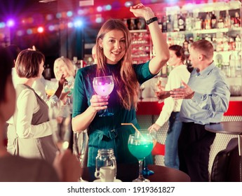 Portrait of smiling girl drinking cocktail and dancing on corporate party