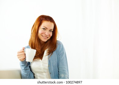 Portrait of a smiling girl enjoying a caffee cup