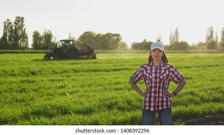 Portrait of a smiling girl farmer in a white cap in a field in spring against the background of a tractor driving across the field.