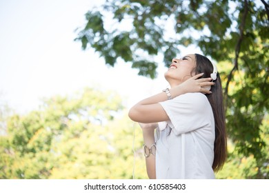 Portrait of a smiling girl with headphones listening to music while relaxing in nature park outdoors.