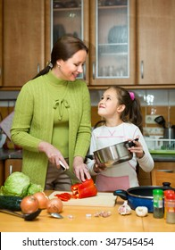 Portrait of smiling girl helping  mom with vegetables and casserole