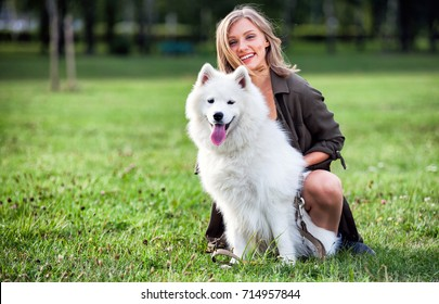 Portrait of smiling girl with her dog at the park outdoor, samoyed