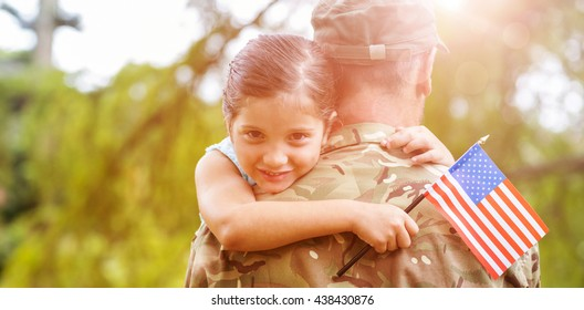 Portrait of smiling girl holding american flag while hugging army officer father in park