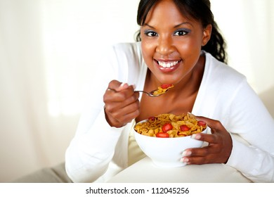 Portrait of a smiling girl looking at you and having healthy breakfast while is sitting on sofa at home indoor. with copyspace