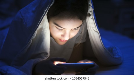 Portrait of smiling girl with mobile phone under blanket at night