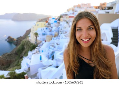 Portrait of smiling girl in Oia village, Santorini. Cute happy tourist girl taking picture during summer vacation in famous European destination Santorini, Greece.