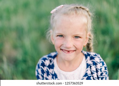 Portrait of a smiling girl on a summer green blurred background