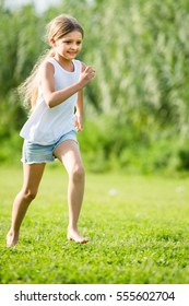 portrait of smiling girl playfully running and jumping on grass in park and looking happy