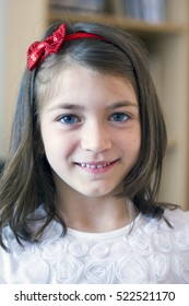 Portrait of a smiling girl with a red ribbon school age