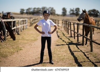 Portrait of smiling girl standing with hands on hips in the ranch