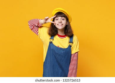 Portrait of smiling girl teenager in french beret, denim sundress showing victory sign isolated on yellow wall background in studio. People sincere emotions, lifestyle concept. Mock up copy space
