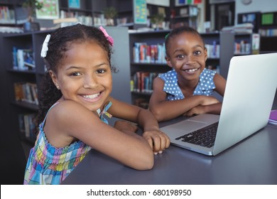 Portrait of smiling girls with laptop at desk in library