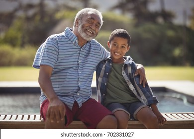 Portrait of smiling grandfather and grandson sitting together on bench
