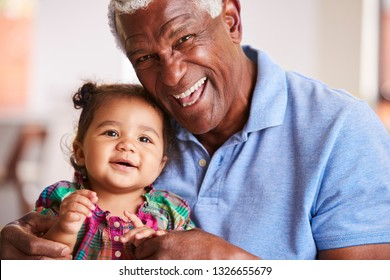 Portrait Of Smiling Grandfather Sitting On Sofa At Home With Baby Granddaughter