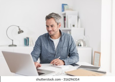 Portrait of a smiling grey hair man with beard, working at home on some project, he is sitting at a white table, drawing ideas on a white notebook, with his laptop in front of him. Focus on the man