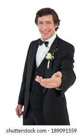 Portrait of smiling groom offering hand over white background